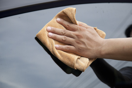 detailing: Hand with microfiber cloth cleaning car.