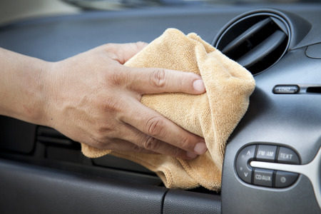 car clean: Hand with microfiber cloth cleaning car.
