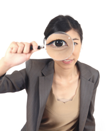 appalled: close-up young woman looking through a magnifying glass isolated