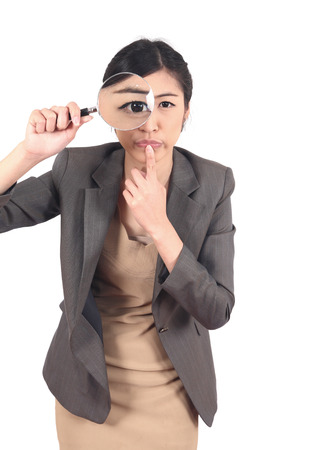 appalled: Confident young woman looking through a magnifying glass isolated  Stock Photo