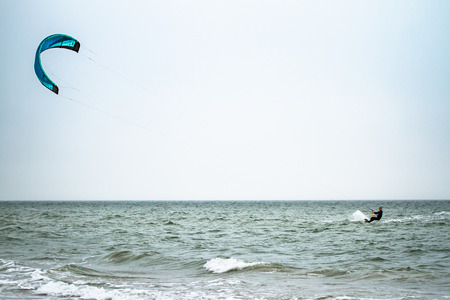 kitesurfer cutting waves from a distance