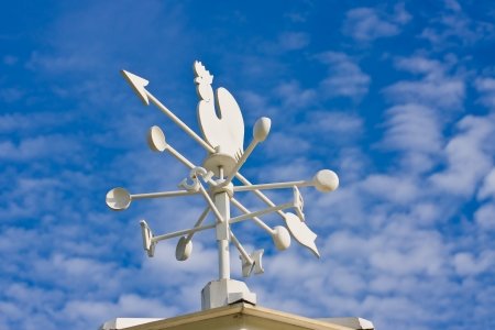 A vintage cockerel wind vane showing the wind direction against a blue sky with clouds.