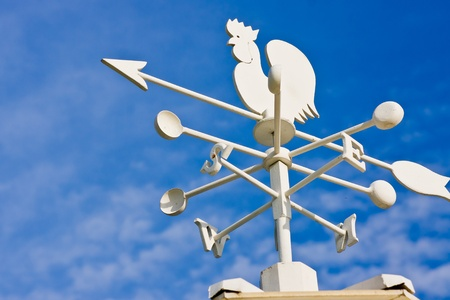 A vintage cockerel wind vane showing the wind direction against a blue sky with clouds. photo