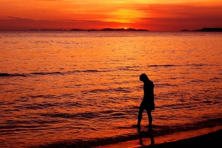 Frau liegt am Strand stehend mit Füßen in den Wellen
