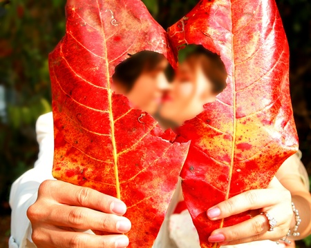 Couple kissing behind the red leaf of wedding Stock Photo