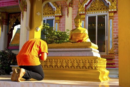 A boy pay respect to the Buddha image photo