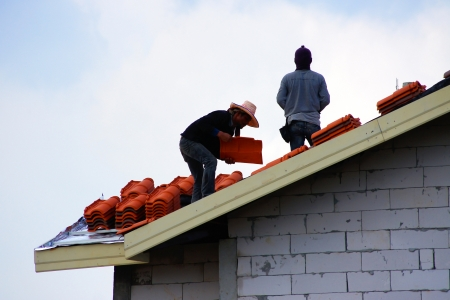 trussing: two workers on roof at works with tile