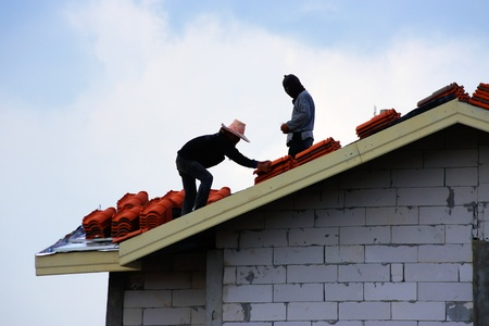 two workers on roof at works with tile