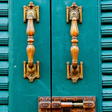 Door handles with an old double door painted with blue photo