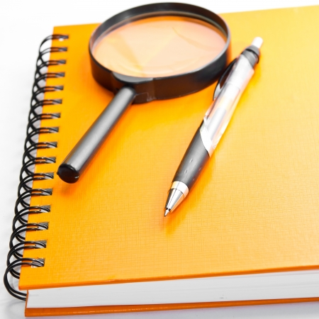orange notebook,pen and glass on isolated white Stock Photo