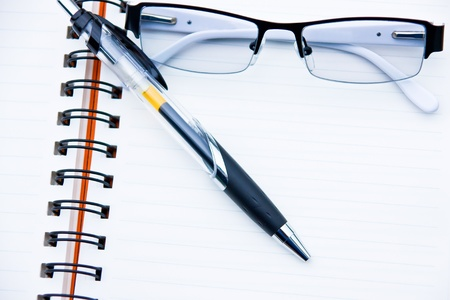 Glasses and pen with notebook photo