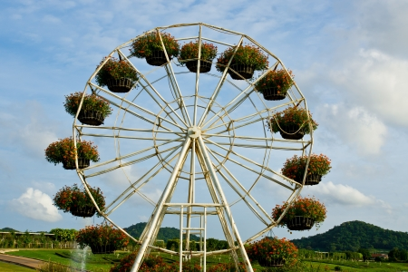 Ferris wheel with basket of flowers on the blue sky background