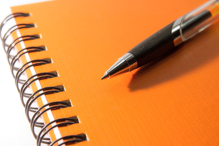 orange Notebook and pen on a white background Stock Photo