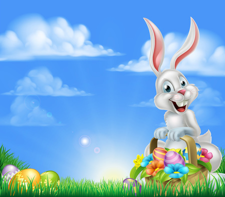 White Easter bunny with a basket full of decorated chocolate Easter eggs in a field Easter background