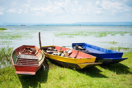 stabilize: Selective in center, colorful small fishing boats with anchor stones to stabilize and dock boats