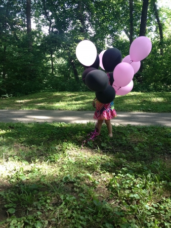 Little girl hiding in a group of balloons
