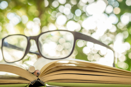 shallow: Close up of open book , pencil and glasses on bokeh background, shallow deep of field on pencil Stock Photo