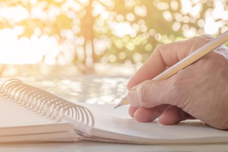 Zblízka rukou psaní na notebook s tužkou Reklamní fotografie
