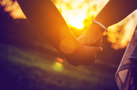 adult hand: Mother holding a hand of her child in sunset