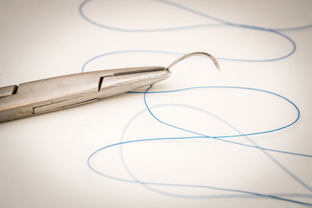 suture: Close up of needle holder with suture and needle Stock Photo