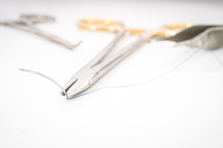 suture: Close up of needle holder with suture and needle, forceps and suture scissors Stock Photo