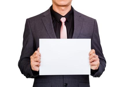 Podnikatel drží prázdný znak papíru v rukou izolovaných na bílém