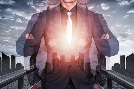 Double exposure of businessman with city and cloud sky