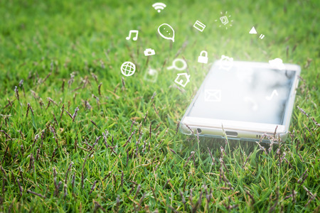 Smart phone with blank screen on green grass background. Reklamní fotografie