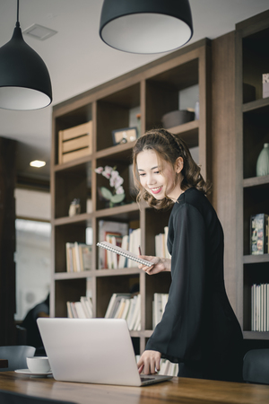 Confident happiness young woman working on laptop or notebook in her office. Beautiful Freelancer Woman working online at her home. Beauty Asian business woman concept.