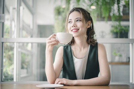 Portrait of Asian woman smiling in coffee shop cafe. Beautiful girl with coffee cup in the morning.