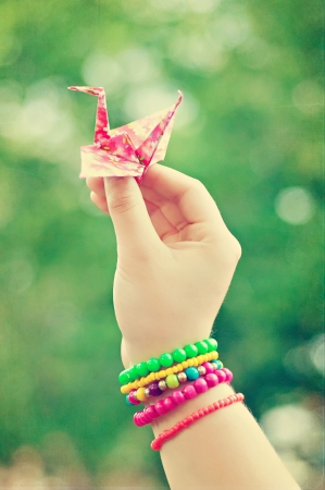 Origami crane in hand with colorful bracelets photo