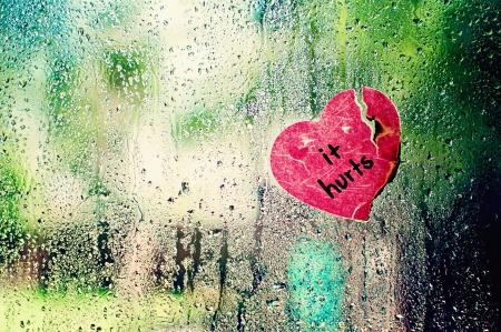 cut paper: Broken heart on rain dropped window Stock Photo