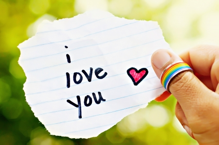 pride: Hand with rainbow ring holding paper that says I love you  Stock Photo