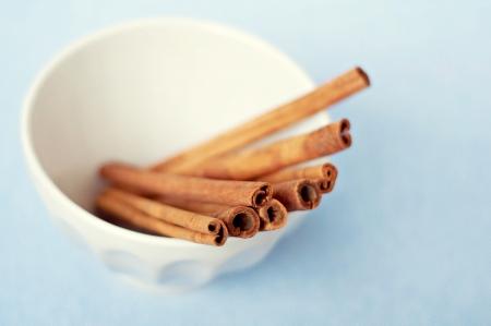 Cinnamon Sticks in Bowl on Blue Background