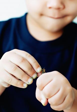 Little boy with caterpillar in hand