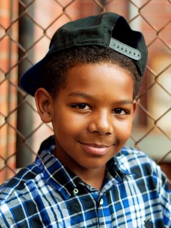 少年野球帽の塀の近くで 写真素材