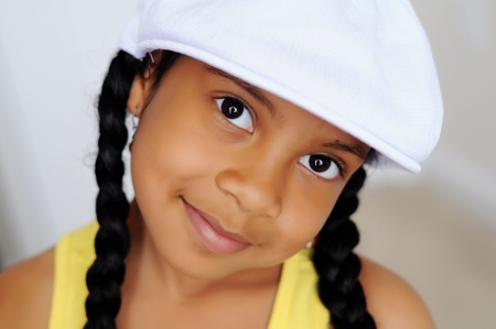 tween girl: Young girl in white hat smiling Stock Photo