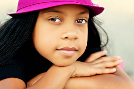 Young girl with arms crossed in pink hat