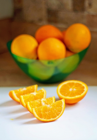 Oranges in bowl with one sliced up