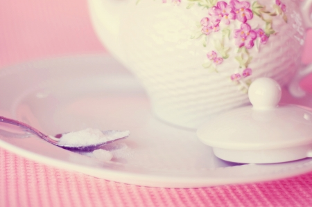 Tea pot with spoon of sugar on plate