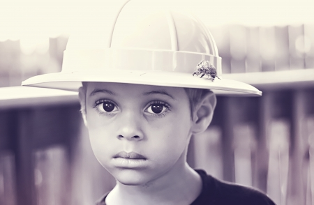 Boy in safari hat with cicada shell on hat
