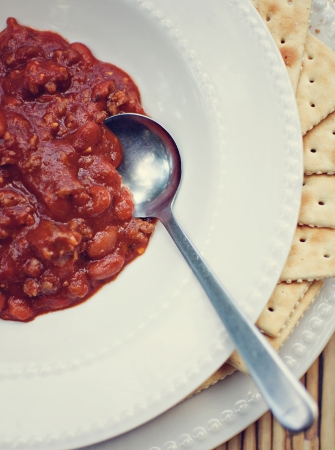 Chili in bowl with spoon and crackers