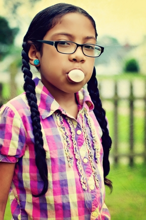 girl with glasses chewing bubble gum  Stock Photo