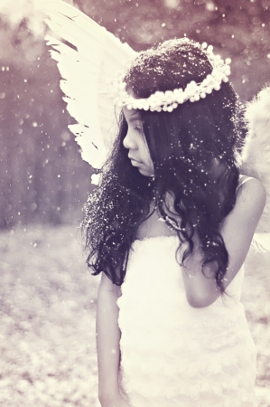 Little girl dressed an angel in snow Stock Photo