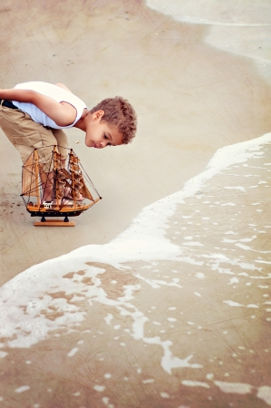 Young boy on beach with toy boat