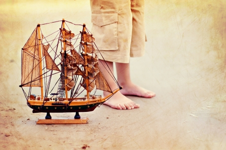boys feet on sand with toy ship at beach Stock Photo