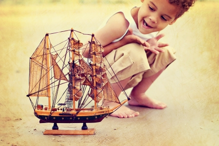 Young boy on beach with toy ship
