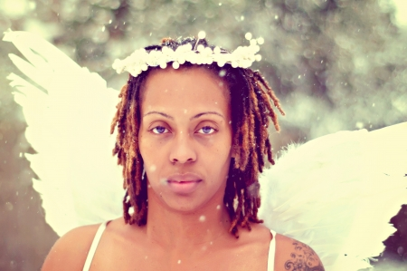 Woman with dreadlocks in snow as an angel