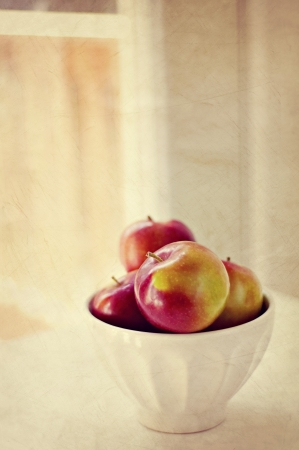 Apples in bowl on table near window