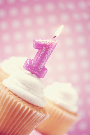 1: Cupcakes with lit number one candle on polka dot background